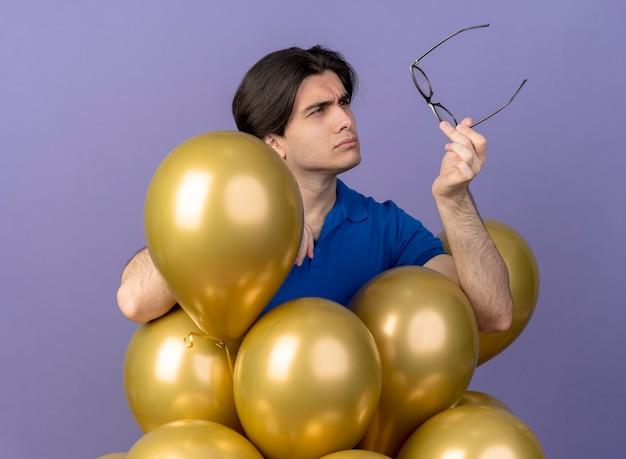 Ahnungsloser, gutaussehender kaukasischer mann steht mit heliumballons, die eine optische brille halten und betrachten