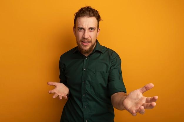 Ahnungsloser hübscher blonder mann hält hände offen und betrachtet kamera auf orange