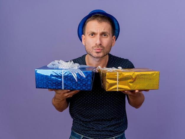 Ahnungsloser hübscher kaukasischer mann, der blauen hut trägt, hält geschenkboxen lokalisiert auf lila hintergrund mit kopienraum