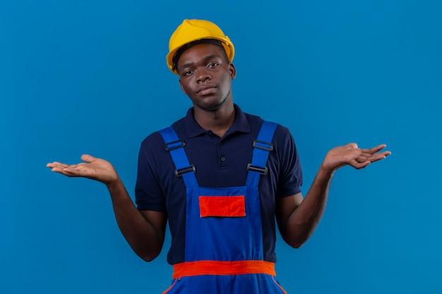 Ahnungsloser junger afroamerikanischer baumeistermann, der bauuniform und sicherheitshelm mit den schultern zuckt, die unsicher und verwirrt aussehen und keine antwort haben, die palmen stehend ausbreitet
