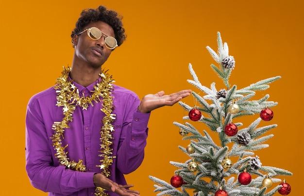 Ahnungsloser junger afroamerikanischer mann, der eine brille mit lametta-girlande um den hals trägt, der nahe verziertem weihnachtsbaum auf orangefarbenem hintergrund steht