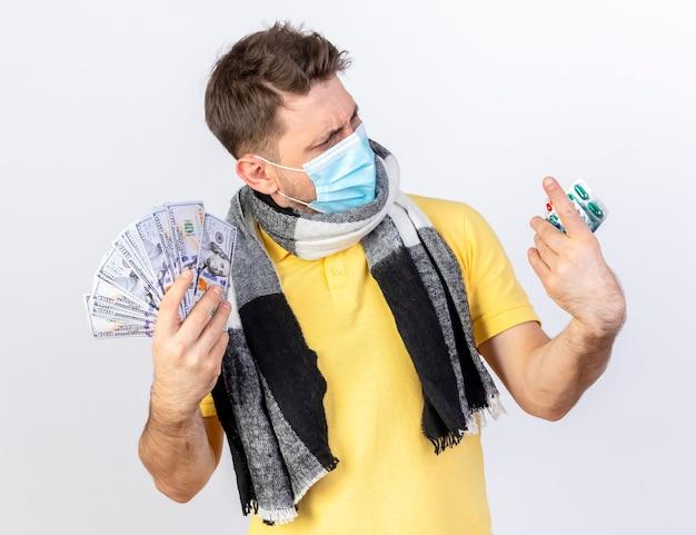 Ahnungsloser junger blonder kranker slawischer mann, der medizinische maske und schal trägt, hält geld und betrachtet packungen von medizinischen pillen, die auf weißer wand mit kopienraum isoliert werden