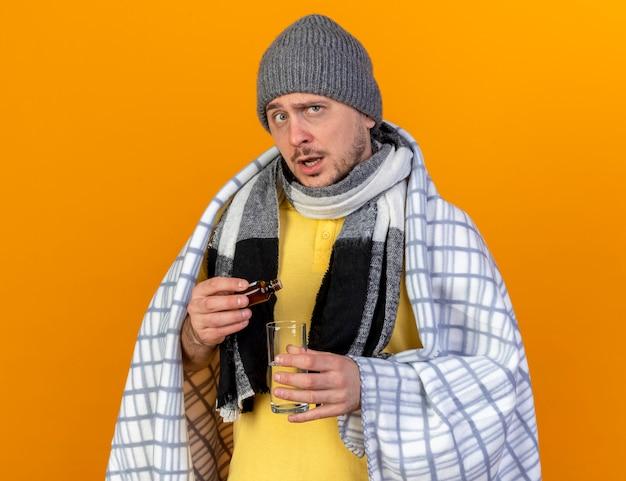 Ahnungsloser junger blonder kranker slawischer mann, der wintermütze und schal in plaid gewickelt hält, hält medizin in glasflasche über glas wasser lokalisiert auf orange wand mit kopienraum