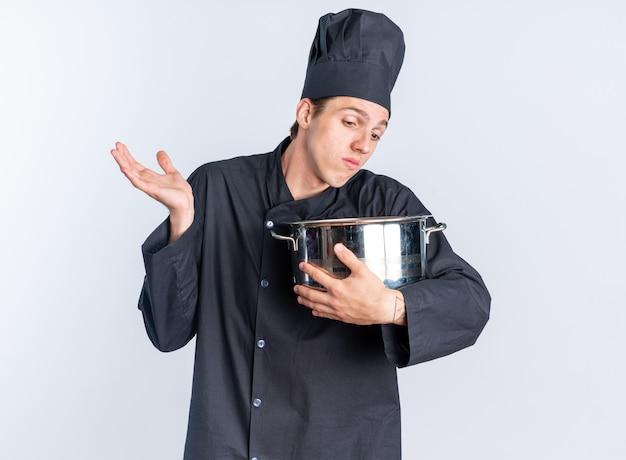 Ahnungsloser junger blonder männlicher koch in kochuniform und mütze, der den topf hält und in den topf schaut, der leere hand zeigt