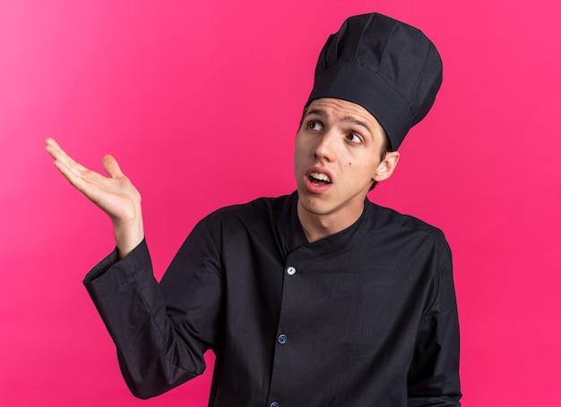 Ahnungsloser junger blonder männlicher koch in kochuniform und mütze, der nach oben schaut und leere hand isoliert auf rosa wand zeigt