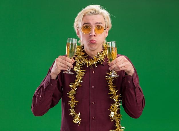 Ahnungsloser junger blonder mann, der eine brille mit lametta-girlande um den hals trägt, hält zwei gläser champagner lokalisiert auf grüner wand