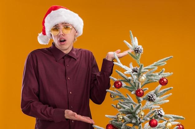 Ahnungsloser junger blonder mann, der weihnachtsmütze und gläser trägt, die nahe verziertem weihnachtsbaum stehen, der lokalisiert auf orange wand zeigt