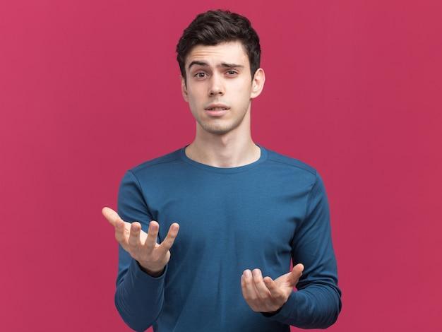 Ahnungsloser junger brünetter kaukasischer junge, der kamera mit händen auf rosa schaut und zeigt