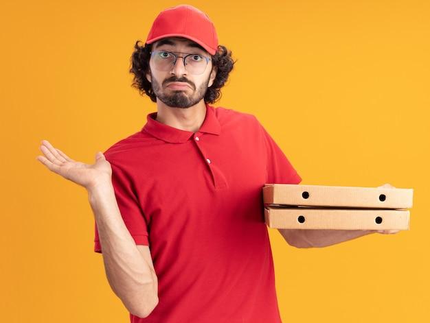 Ahnungsloser junger kaukasischer liefermann in roter uniform und mütze mit brille, die pizzapakete hält, die leere hand einzeln auf oranger wand zeigen?