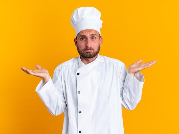 Ahnungsloser junger kaukasischer männlicher koch in kochuniform und mütze mit blick auf die kamera, ich weiß nicht, geste isoliert auf oranger wand?