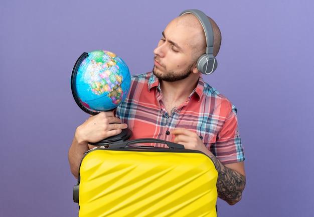 Ahnungsloser junger kaukasischer reisender mit kopfhörern, der den globus hält und betrachtet, der hinter einem koffer steht, isoliert auf violettem hintergrund mit kopierraum