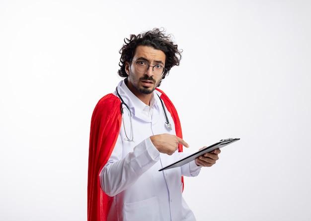 Ahnungsloser junger kaukasischer superheldenmann in optischer brille, der eine arztuniform mit rotem umhang trägt und mit stethoskop um den hals hält und auf die zwischenablage zeigt