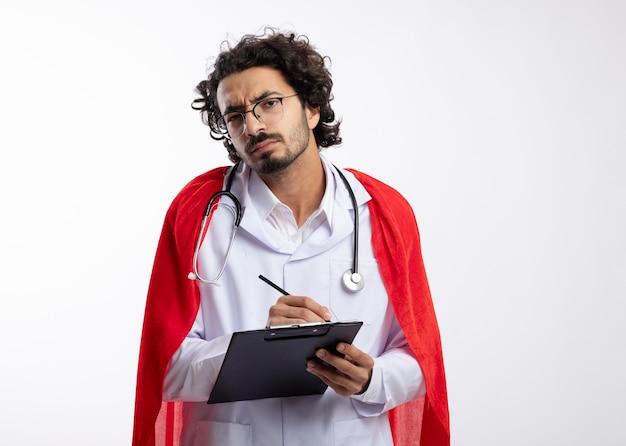Ahnungsloser junger kaukasischer superheldenmann in optischer brille, der eine arztuniform mit rotem umhang und mit stethoskop um den hals trägt, hält bleistift und zwischenablage