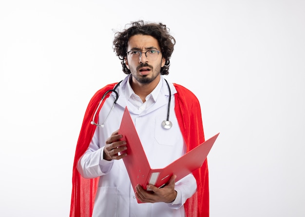 Ahnungsloser junger kaukasischer superheldenmann in optischer brille in arztuniform mit rotem mantel und mit stethoskop um den hals hält aktenordner