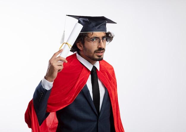 Ahnungsloser junger kaukasischer superheldenmann in optischer brille mit anzug mit rotem mantel und abschlusskappe hält diplom