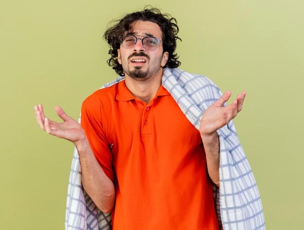 Ahnungsloser junger kranker mann, der eine brille trägt, die in das plaid eingewickelt ist, das front betrachtet, die leere hände lokalisiert auf olivgrüner wand zeigt