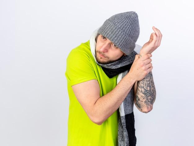 Ahnungsloser junger kranker mann, der wintermütze und schal trägt, hält hand, die versucht, puls isoliert auf weißer wand zu hören