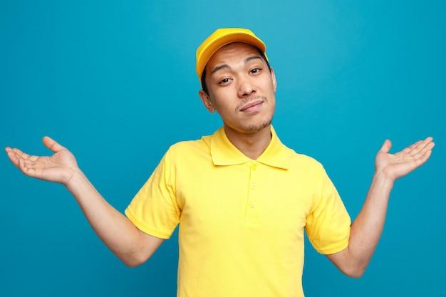 Ahnungsloser junger lieferbote, der uniform und mütze trägt und keine geste kennt