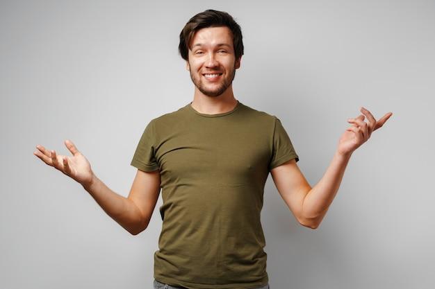 Ahnungsloser junger mann gestikuliert ich weiß nicht gegen grau