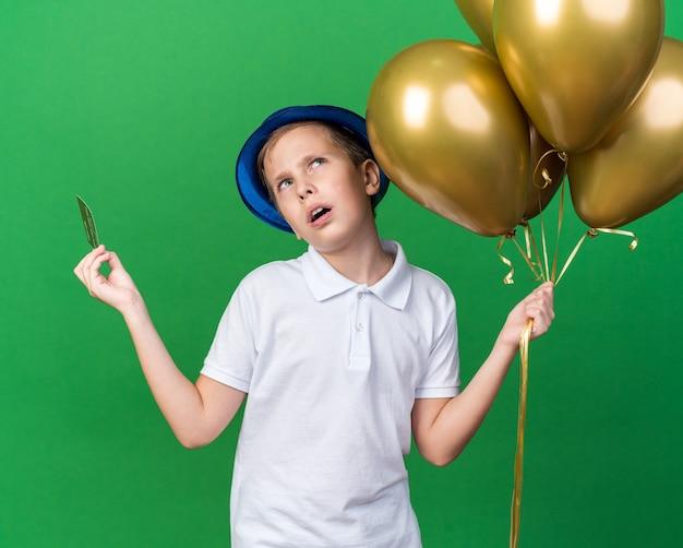 Ahnungsloser junger slawischer junge mit blauem partyhut, der heliumballons und kreditkarte hält, die isoliert auf grüner wand mit kopienraum nachschlagen