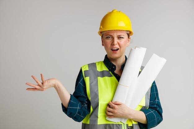 Ahnungsloser junger weiblicher bauarbeiter, der sicherheitshelm und sicherheitsweste hält, die papiere hält, die leere hand zeigen