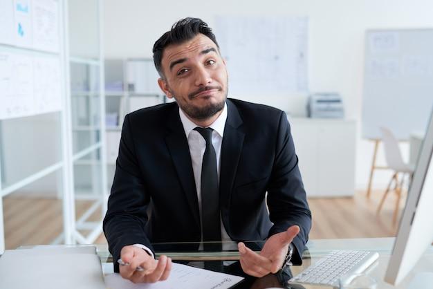 Ahnungsloser kaukasischer geschäftsmann, der am schreibtisch im büro sitzt und kamera betrachtet