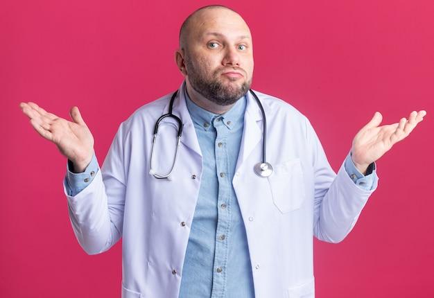 Ahnungsloser männlicher arzt mittleren alters, der medizinische robe und stethoskop trägt, ich weiß nicht, geste isoliert auf rosa wand