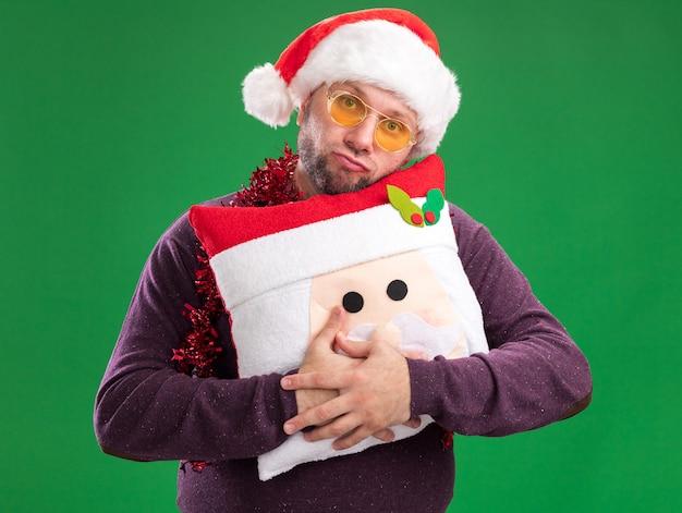 Ahnungsloser mann mittleren alters, der weihnachtsmütze und lametta-girlande um den hals mit gläsern trägt, die weihnachtsmann-kissen halten, lokalisiert auf grüner wand