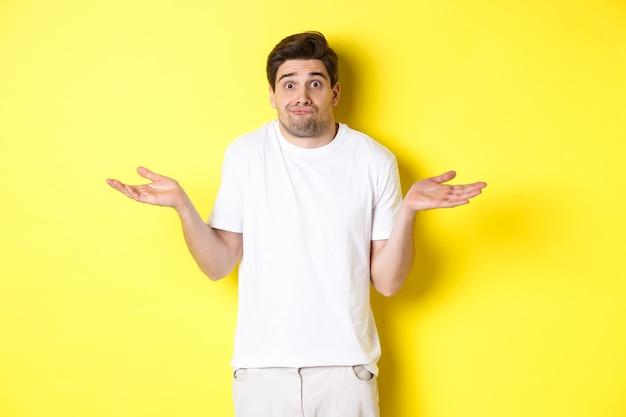 Ahnungsloser mann zuckt die achseln, breitet verwirrt die hände zur seite, weiß nichts und steht über gelb