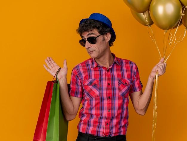 Ahnungsloser parteimann mittleren alters, der partyhut und sonnenbrille hält, die luftballons und papiertüten hält, die front betrachten, die leere hand lokalisiert auf orange wand zeigt