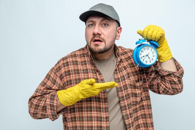 Ahnungsloser slawischer putzmann mit gummihandschuhen, der den wecker hält und zeigt