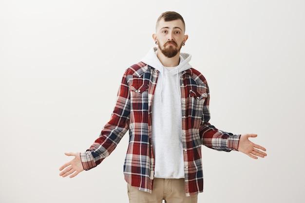 Ahnungsloser und verwirrter hipster-typ zuckt die achseln und spreizt die hände seitwärts, ohne es zu merken