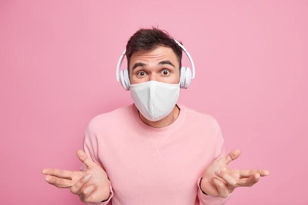Ahnungsloser zögerlicher junger mann breitet handflächen aus sieht verwirrt aus hört musik über drahtlose kopfhörer bleibt zu hause, um die coronavirus-krankheit nicht zu verbreiten, trägt schutzmaske