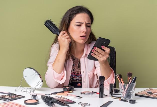 Ahnungsloses junges brünettes mädchen, das am tisch mit make-up-tools sitzt und kamm hält und das telefon isoliert auf olivgrüner wand mit kopienraum anschaut