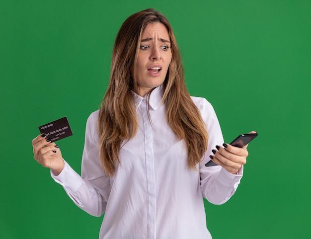 Ahnungsloses junges hübsches kaukasisches mädchen hält kreditkarte und schaut auf das telefon isoliert auf grüner wand mit kopierraum