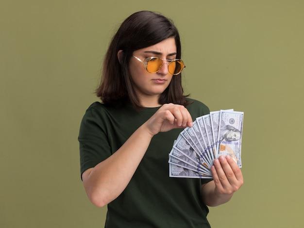 Ahnungsloses junges hübsches kaukasisches mädchen in der sonnenbrille, die geld auf olivgrün hält und betrachtet