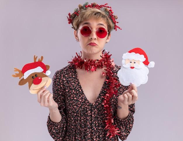 Ahnungsloses junges hübsches mädchen mit weihnachtskopfkranz und lametta-girlande um den hals mit brille, die weihnachtsren und weihnachtsmann-papierverzierungen isoliert auf weißer wand hält holding