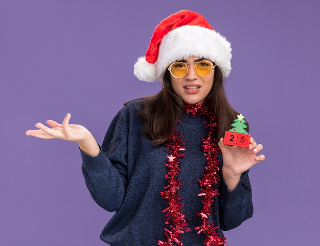 Ahnungsloses junges kaukasisches mädchen in sonnenbrille mit weihnachtsmütze und girlande um den hals hält weihnachtsbaumschmuck isoliert auf lila wand mit kopierraum