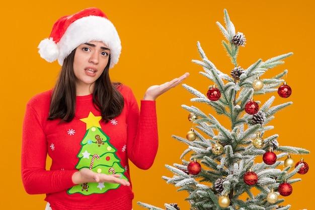 Ahnungsloses junges kaukasisches mädchen mit weihnachtsmütze, die auf weihnachtsbaum lokalisiert auf orange hintergrund mit kopienraum zeigt