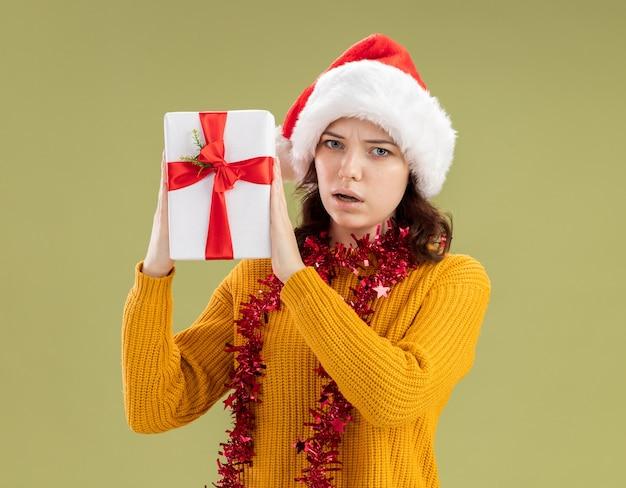 Ahnungsloses junges slawisches mädchen mit weihnachtsmütze und mit girlande um hals, die weihnachtsgeschenkbox lokalisiert auf olivgrünem hintergrund mit kopienraum hält