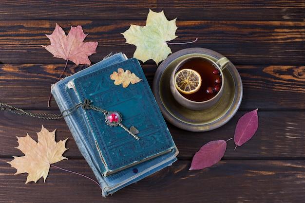 Ahornblätter, alte bücher und tee in einer tasse mit zitrone