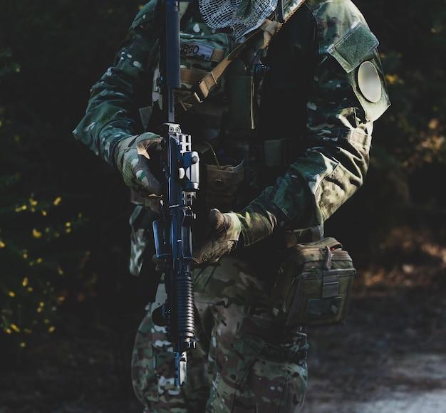 Airsoft-militärspieler in tarnuniform mit bewaffnetem sturmgewehr.