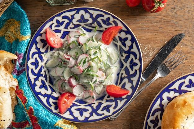 Ak bura - traditioneller usbekischer salat aus radieschen, gurken, knoblauch, tomaten und kräutern mit saurer sahne