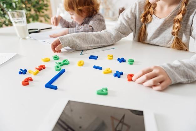 Akademischer spaß. clevere neugierige begeisterte dame, die mathe lernt, während sie bunte plastiknummern arrangiert und mit ihrem bruder am tisch sitzt