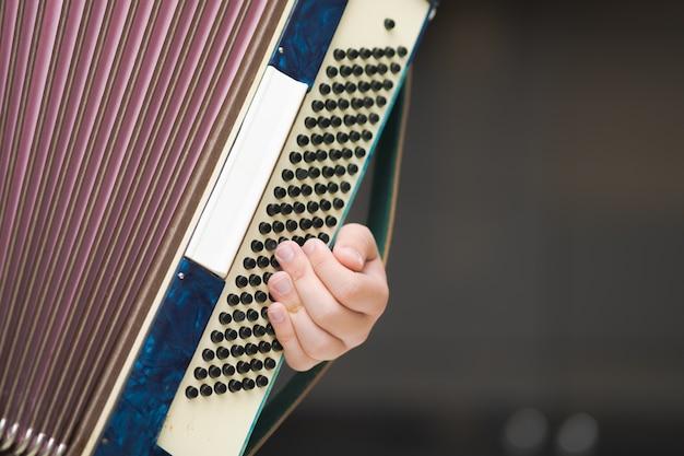 Akkordeon in den händen eines musikers, nahaufnahme.