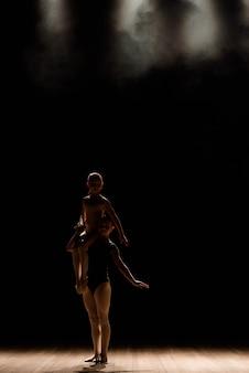 Akrobatischer tanz. tanz mit elementen der akrobatik. mädchen, die tanzunterstützung tun.
