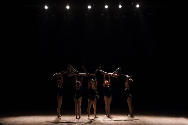 Akrobatischer tanz. tanzen sie mit elementen der akrobatik. mädchen, die tanzunterstützung tun.