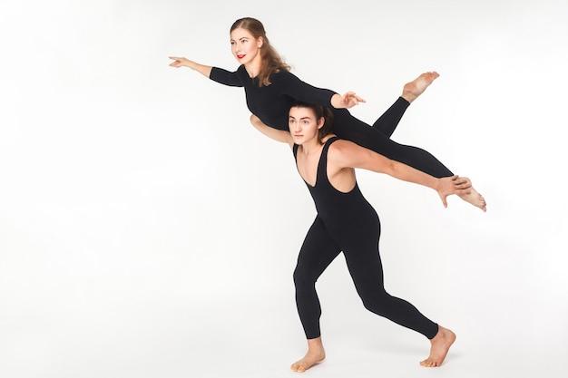Akrobatisches konzept, fliegenpose. junger mann, der frau hält und balanciert. studioaufnahme, isoliert auf weißem hintergrund