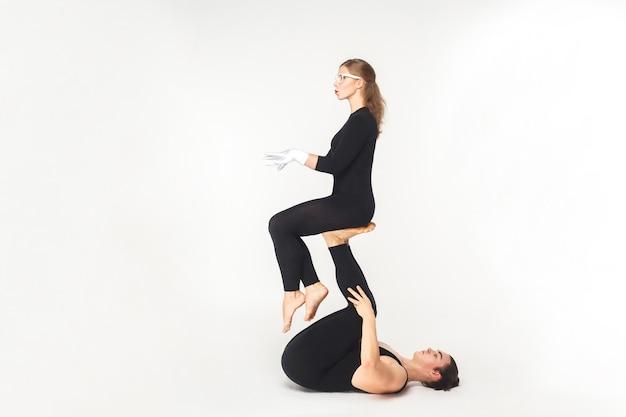 Akrobatisches konzept, sitzhaltung. junger mann, der frauenbeine hält, balancierend. studioaufnahme, isoliert auf weißem hintergrund