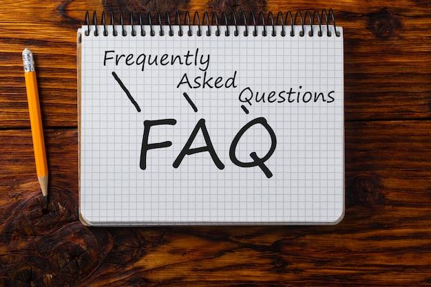 Akronym faq in bleistift in einem notizbuch geschrieben.